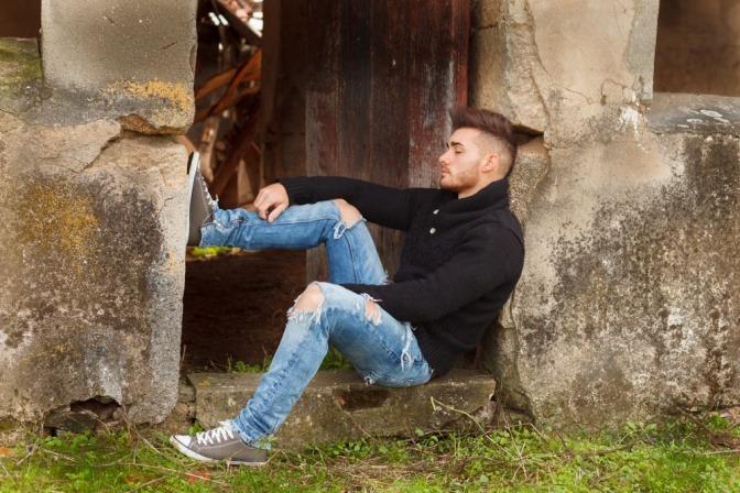 Ein Mann sitzt vor einer Tür