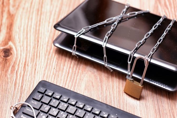 Ketten sind um Smartphone und Laptop gelegt