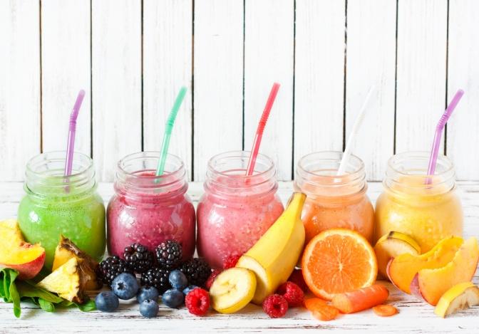 Verschieden färbige Smoothies stehen nebeneinander, im Vordergrund liegt Obst