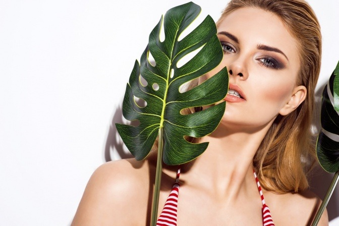 Frau im Sommer hinter Palmblatt