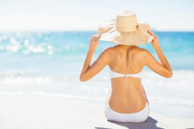 Frau am Strand mit Sonnenhut.