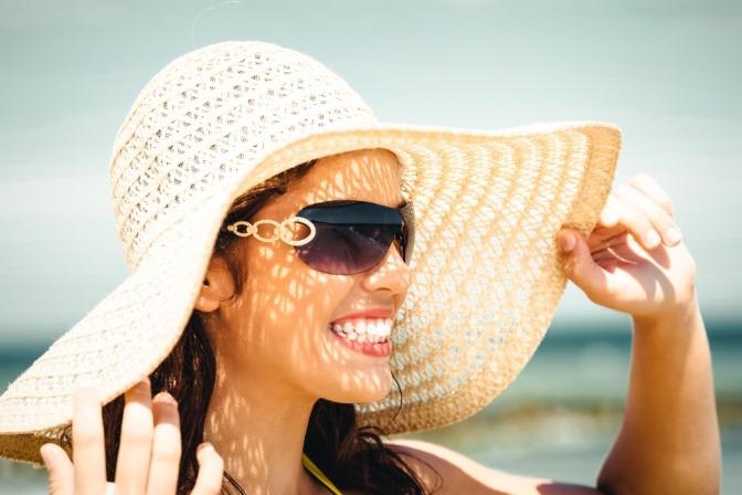 Frau mit Sonnenhut und Sonnenbrille