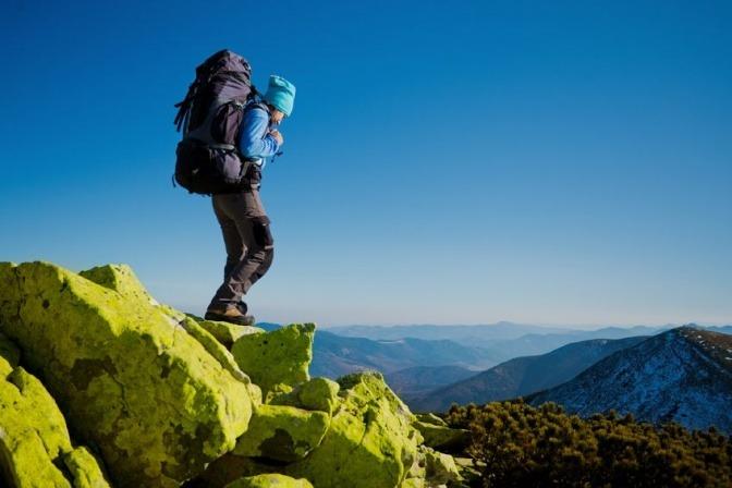 Ein Mann ist im Gebirge und verwendet Sonnenschutz