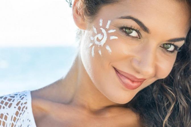 Frau mit Sonnencreme in Form einer Sonne im Gesicht
