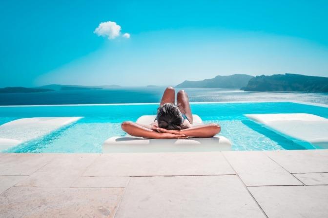 Frau auf einer Liege am Pool