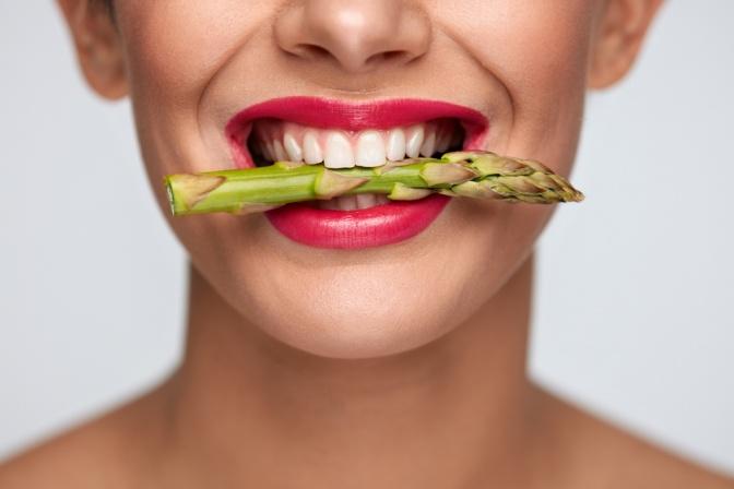 Eine Frau hat Spargel zwischen den Zähnen