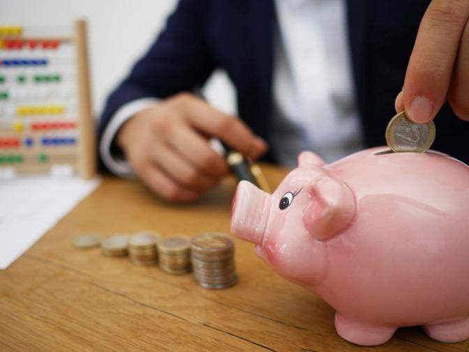 Jemand wirft Geld in ein Sparschwein