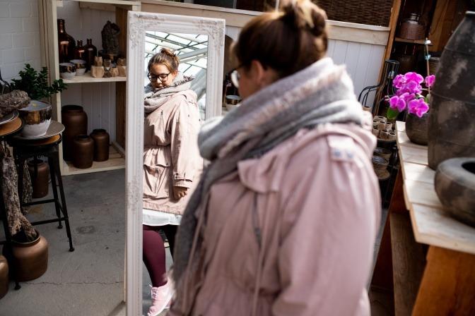 Eine Frau mit Lipödem sieht sich in den Spiegel