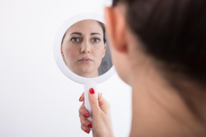 Eine Frau schaut ihr Gesicht in einem Handspiegel an