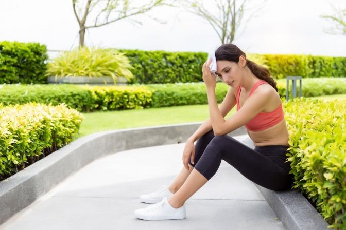 Frau mit Übelkeit nach Sport bei Hitze