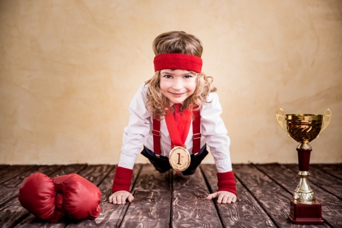 Ein Kind mit mehreren Medaillen um den Hals macht Liegestütze und lächelt dabei.