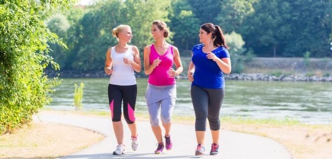 Drei Frauen betreiben Sport für Übergewichtige und laufen an einem sonnigen Tag gemeinsam durch einen Park.