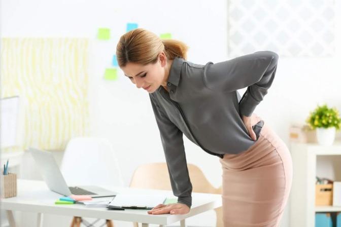 Eine Frau beugt sich in einer Büroumgebung über einen Schreibtisch. Sie stützt sich mit einer Hand ab, während die andere den hinteren unteren Rücken stützt. Es wirkt, als ob die Frau von Sport gegen Rückenschmerzen profitieren könnte.
