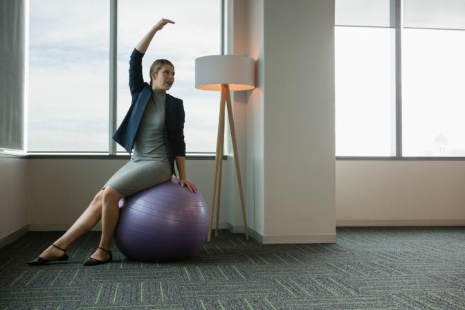 Eine Frau im Businessoutfit macht Übungen auf einem Gymnastikball.