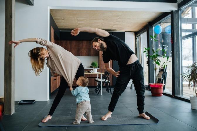 Ein Paar macht Sport gegen Stress, ein Kind zerrt währenddessen am Trikot der Mutter.