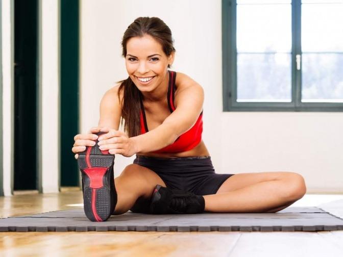 Eine junge Frau sitzt in einer Turnhalle oder im Fitnessstudio auf dem Boden und dehnt sich das rechte Bein.