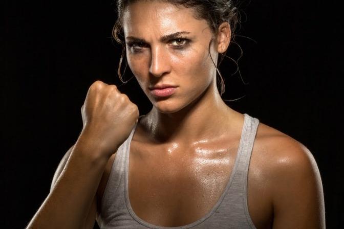 Das Bild zeigt den Oberkörper einer jungen Frau, die gerade ein schweißtreibendes Workout vollzogen hat und nun voller Überzeugung und Tatendrang in die Kamera blickt.