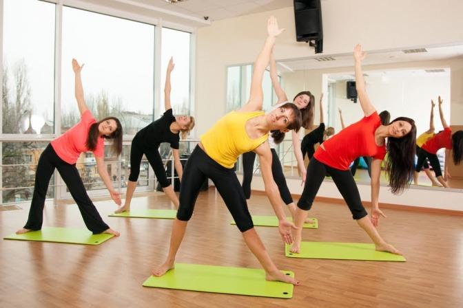 Mehrere Frauen sind in einem Fitnessraum und machen gemeinsam Dehnübungen.