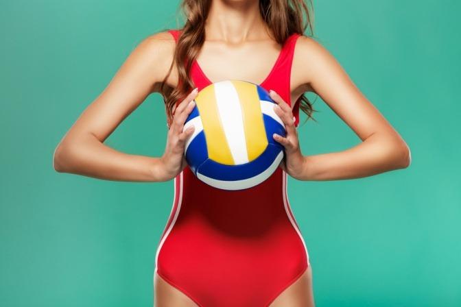 Frau in rotem Badeanzug mit Ball