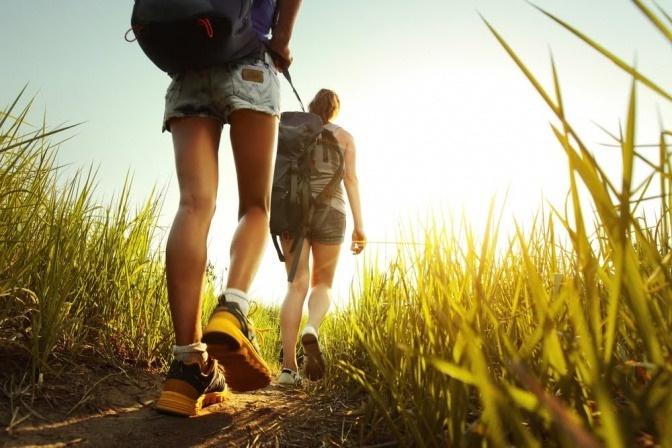 Zwei Menschen wandern mit der richtigen Sportkleidung bei Hitze