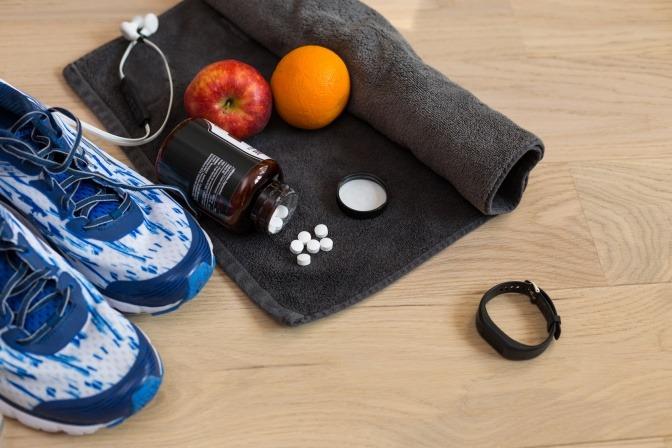 Sportsachen liegen neben Obst und Tabletten