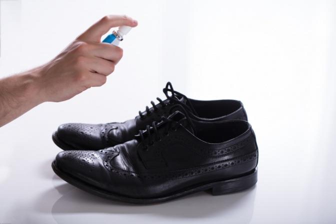 Ein Mann sprüht Spray auf einen Schuh