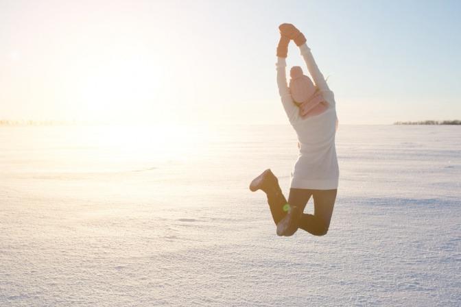 Eine Frau mit einem fröhlichen Gesichtsausdruck springt mitten auf einer Wiese in die Luft.
