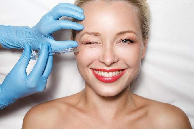 Eine blonde und gut gelaunte Frau erhält eine Injektion unter der rechten Auge.