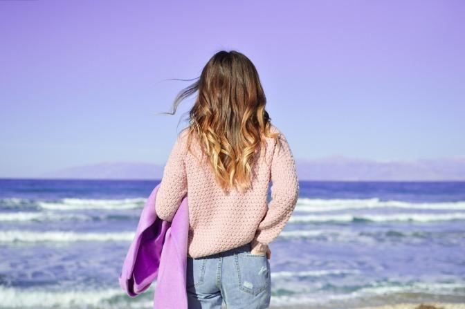 Eine Frau neben dem Meer trägt Kleidung