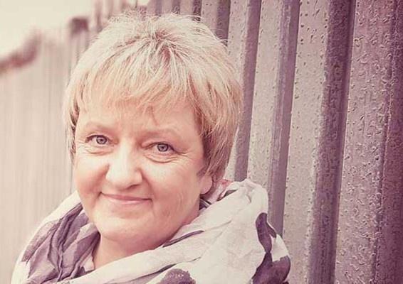 Stefanie Menzel steht vor einer Wellblechwand und lächelt in die Kamera