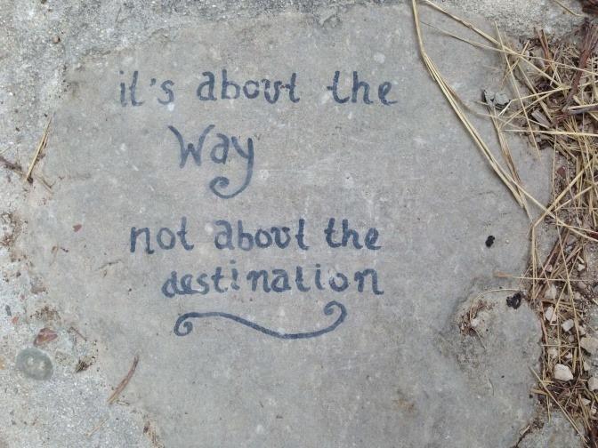 Auf einem Stein am Jakobsweg steht ein Spruch
