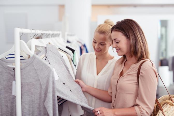 Eine Frau lässt sich beim Kleiderkauf zu ihrem Stil beraten