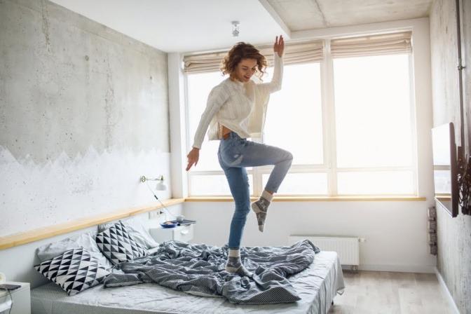 Eine Frau tanzt auf ihrem Bett.