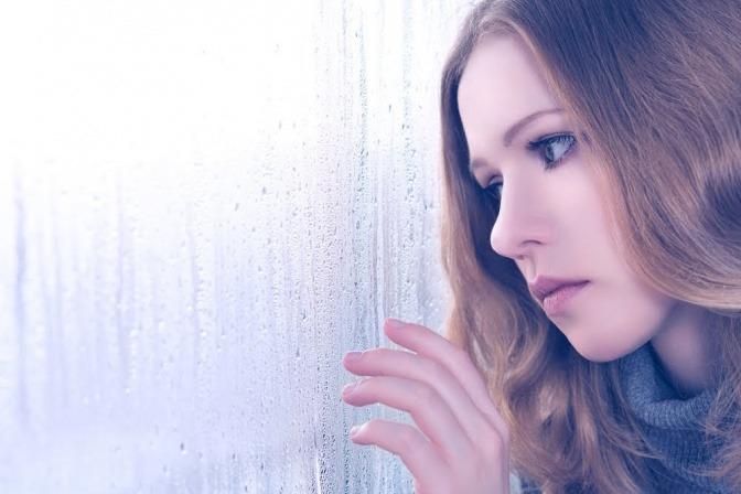 Eine Frau lehnt an einem von Regentropfen benetzten Fenster.