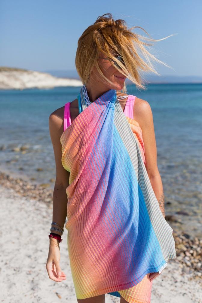 Frau mit buntem Strandtuch aus Stoff in Bio-Qualität