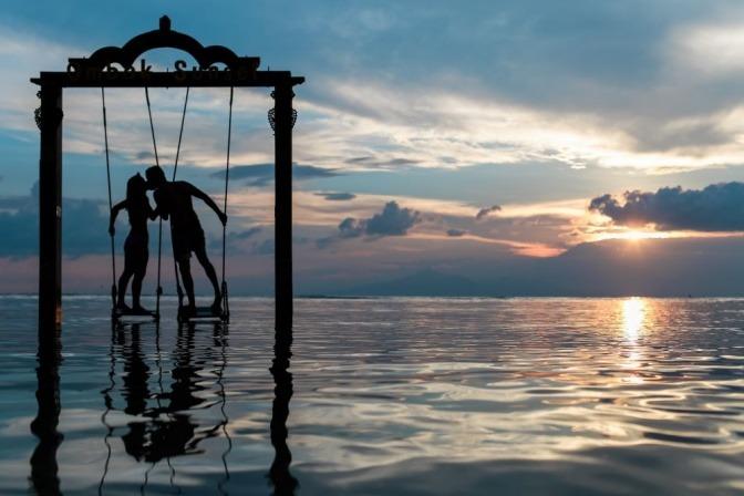 Ein Paar sitzt im Urlaub auf einer Schaukel und küsst sich
