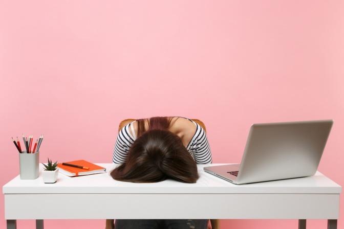 Frau am Schreibtisch überfordert fördert Akne durch Stress