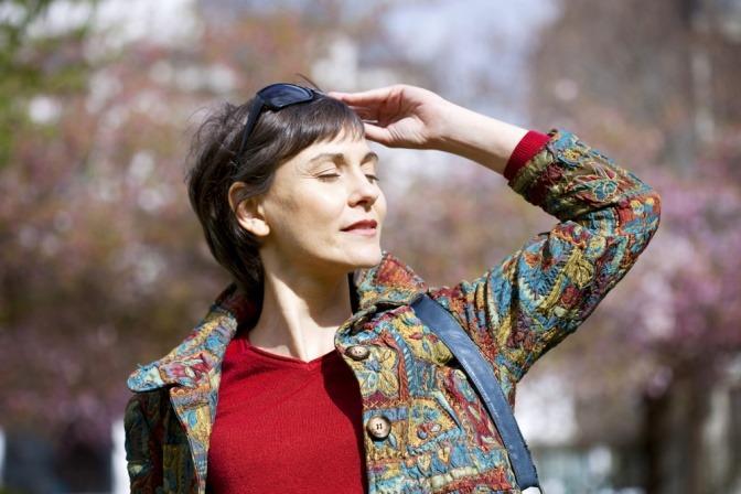 Eine Frau blickt entspannt in die Sonne um Stress zu reduzieren