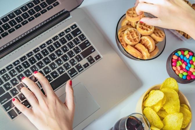 Frau am Schreibtisch mit vielen Süßigkeiten.