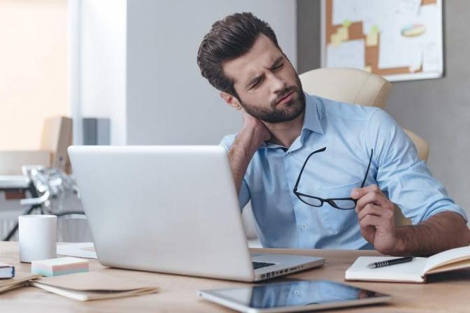 Ein Mann sitzt vor einem Laptop und wirkt gestresst