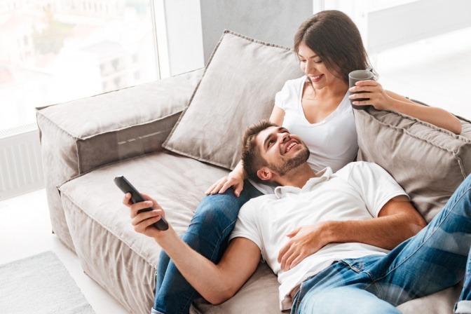 Ein Paar sitzt auf der Couch, die Fernbedienung in der Hand