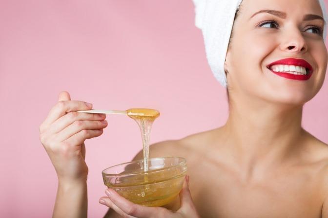 Junge Frau mit Zuckerpaste auf Spatel.