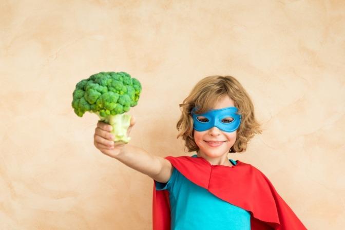Ein Kind im Superheldenkostüm hält einen Brokkoli hoch.