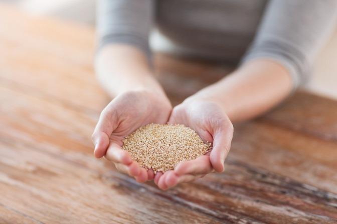 Eine Frau hält Quinoa-Samen in ihren Händen.