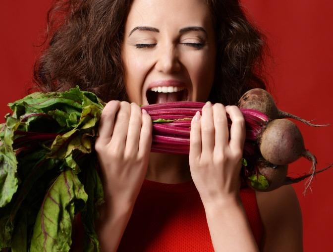 Eine junge Frau versucht, in ein Bündel rohe rote Beete zu beißen.
