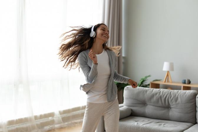 Junge Frau mit Kopfhörern tanzt glücklich im Wohnzimmer