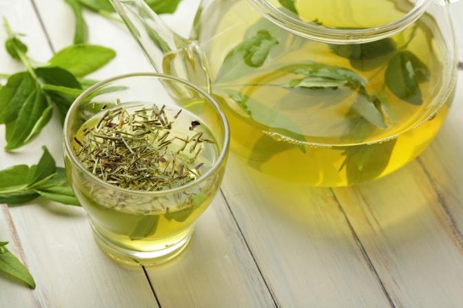 Ein Glas mit Tee steht neben einer Glaskanne Tee, darin liegen grüne Blätter