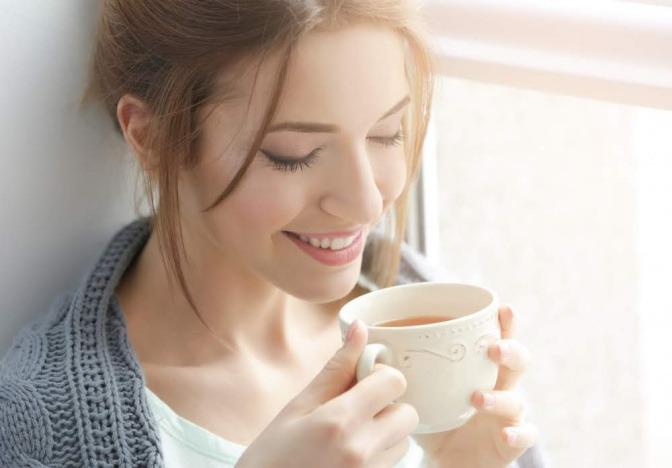 Frau trinkt aus einer Tasse.