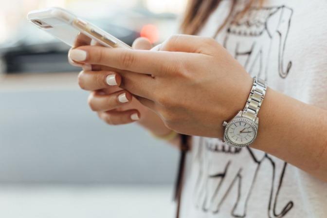 Eine Frau tippt auf Ihrem Telefon bzw. Smartphone