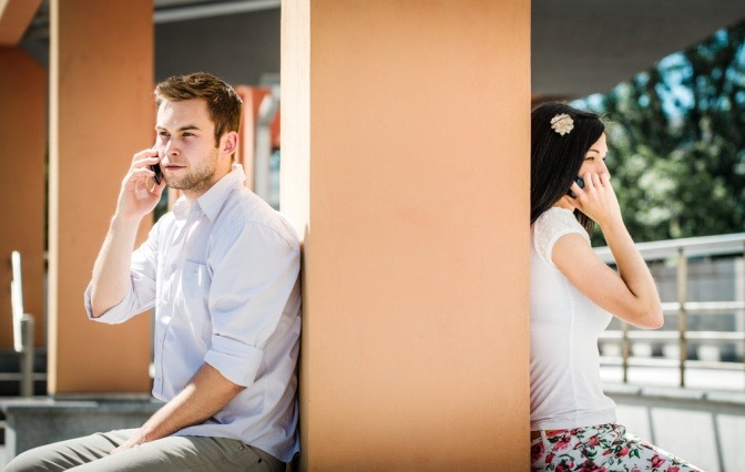 Ein Paar telefoniert miteinander, obwohl es nur durch eine dünne Wand getrennt ist.